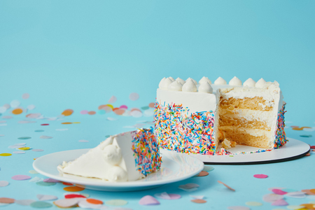 Slice of cake with cut cake on blue background with confetti Stok Fotoğraf