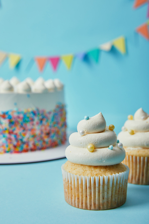 Delicious cupcake with sugar sprinkles on blue background with cake and bunting