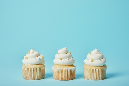 Tasty cupcakes with sugar sprinkles on blue background 免版税图像