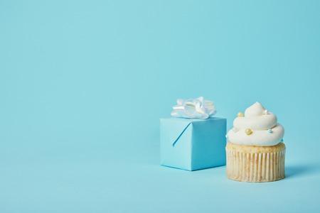 Gift box with white bow and delicious cupcake on blue background Stock Photo