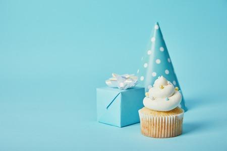 feestmuts, geschenkdoos en heerlijke cupcake op blauwe achtergrond