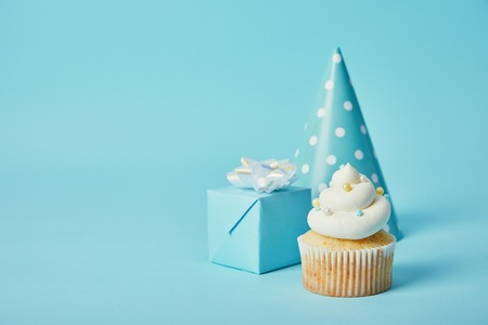 party hat, gift box and delicious cupcake on blue background Stockfoto
