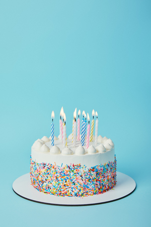 Tasty birthday cake with lighting candles on blue background