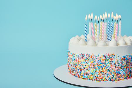 Heerlijke verjaardagstaart met kaarsen aansteken op blauwe achtergrond
