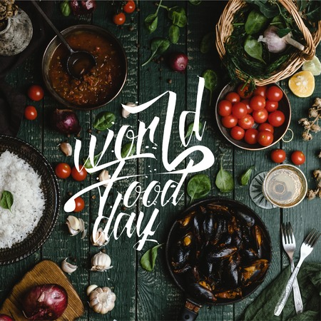 Top view of cooked mussels with shells served in pan with tomatoes, herbs and wine on wooden table, world food day lettering Фото со стока