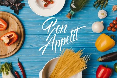 Draufsicht auf rohe Nudeln und Gemüse auf blauem Tisch, guten Appetit Schriftzug Standard-Bild