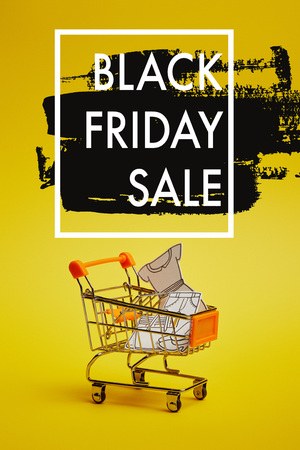 close up view of little shopping trolley with paper clothes on yellow backdrop, black friday sale inscription Фото со стока