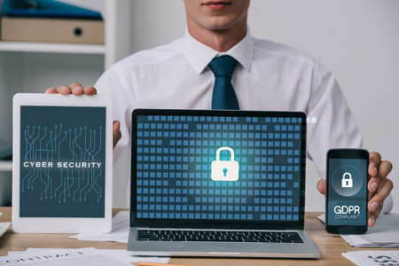 cropped shot of businessman showing laptop, tablet and smartphone with gdpr and cyber security signs on screens at workplace in office