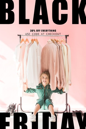 cheerful charming kid in trendy overalls sitting under clothes on hangers, black friday sale banner
