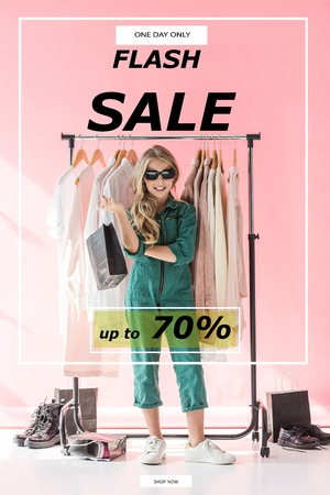 stylish child in overalls and sunglasses standing with shopping bag near clothes and footwear in boutique, flash sale banner concept