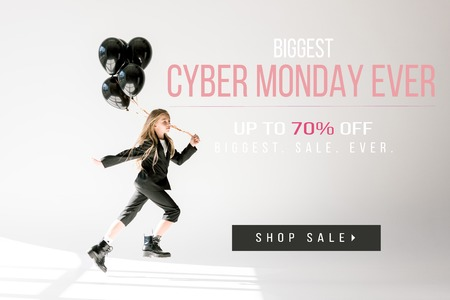 fashionable child in trendy suit jumping with black balloons on grey, black friday sale banner 免版税图像