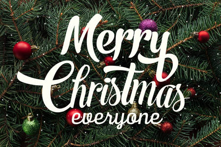 full frame of colorful christmas toys on green pine tree branches with merry christmas everyone lettering