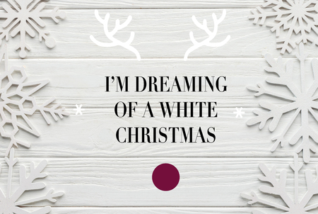 flat lay with decorative snowflakes on white wooden background with Im dreaming of a white christmas inspiration