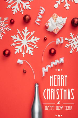 top view of present, champagne bottle, red christmas toys, white ribbons and decorative snowflakes arranged isolated on red with merry christmas and happy new year lettering