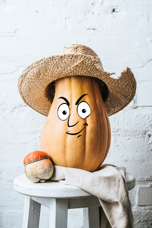 close up view of ripe pumpkins with drawn smiley facial expression and straw hat on wooden stool and white brick wall backdrop Stockfoto