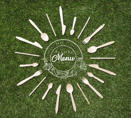 top view of wooden spoons with forks and knives in shape of sun lying on grass, menu inscription Stockfoto