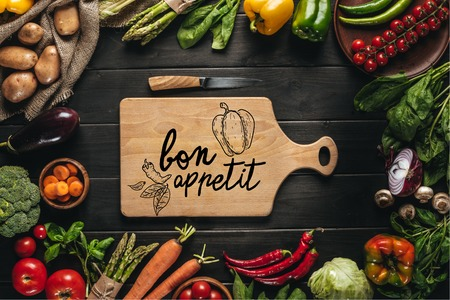 top view of cutting board with knife and organic fresh vegetables around on wooden tabletop, bon appetit lettering
