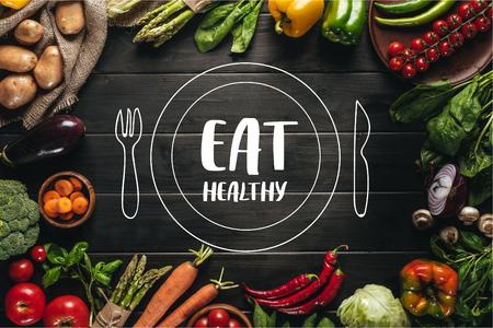 frame of organic fresh vegetables on sacking on wooden tabletop with eat healthy lettering with drawn plate and cutlery Фото со стока
