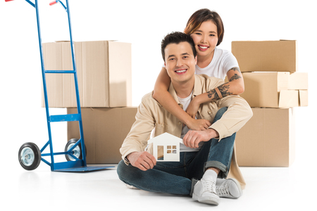 couple hugging and holding house model with cardboard boxes on background, moving to new house concept Stok Fotoğraf