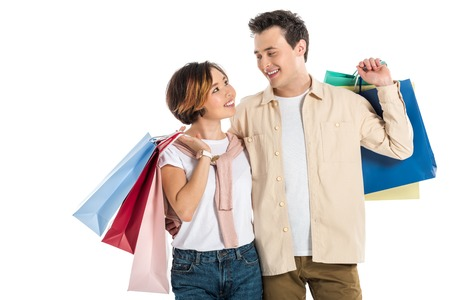 smiling couple looking at each other and carrying shopping bags isolated on white