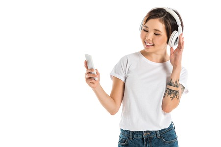 happy young woman wearing headphones, listening music and using smartphone isolated on white