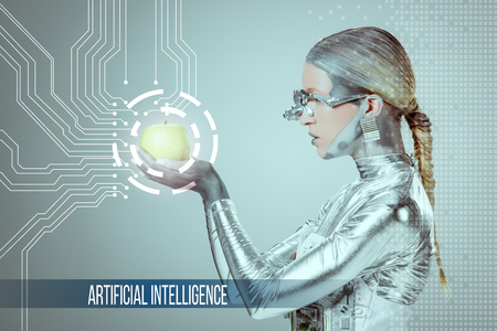 side view of cyborg holding and examining green apple with digital data isolated on grey with