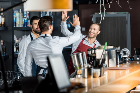 handsome smiling barmen in aprons high five at workplace Фото со стока