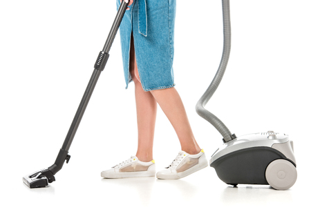low section of young woman using vacuum cleaner isolated on white 写真素材