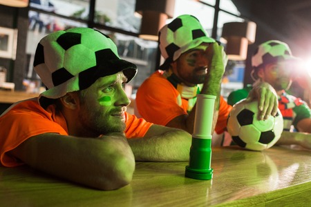 Football fans sitting in hats, watching soccer in bar