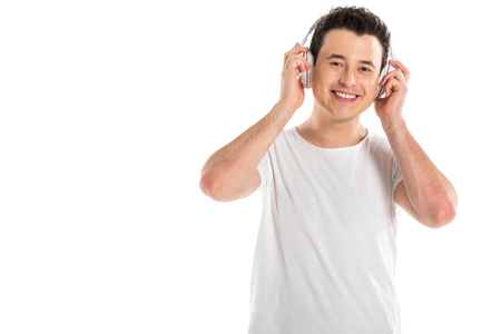cheerful handsome man in headphones listening to music isolated on white