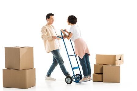 husband holding wife on hand truck with cardboard boxes on background, moving to new house concept