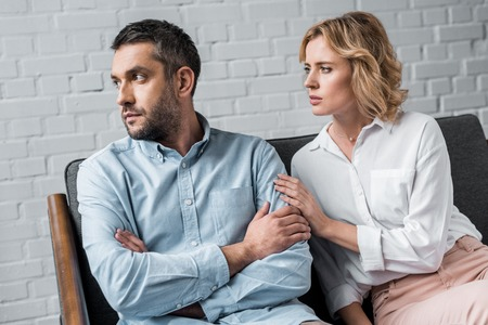 woman talking to husband while sitting on couch after quarrel