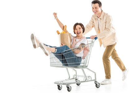 smiling husband pushing shopping cart with wife inside holding groceries isolated on white, couple having fun