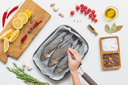 partial view of woman putting salting uncooked fish in baking tray on table with ingredients
