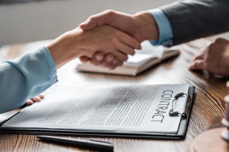 Nahaufnahme der Zwischenablage mit Vertrag und Anwalt mit dem Kunden, der die Hände schüttelt