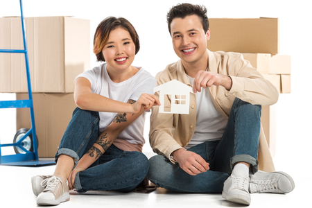 husband and wife holding house model with cardboard boxes on background, moving to new house concept Stok Fotoğraf
