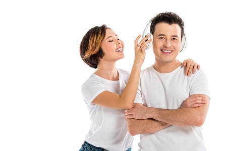 happy wife putting headphones on smiling husband isolated on white