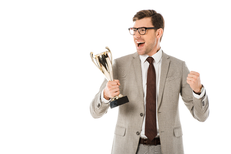 excited successful businessman in grey suit holding trophy cup isolated on white Imagens