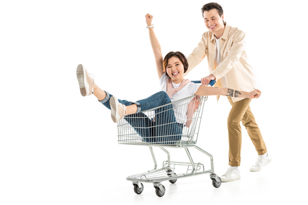 husband pushing shopping cart with happy wife inside isolated on white, couple having fun Stockfoto