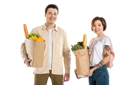 happy husband and wife holding grocery bags and looking at camera isolated on white