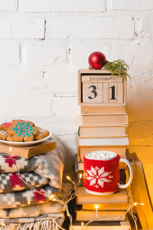 pile of books, blanket, gingerbread cookies, cup of hot chocolate with marshmallows, calendar with 31 december and christmas bauble