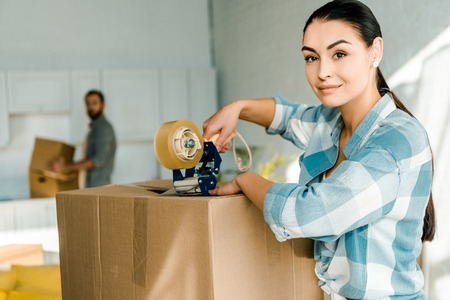 wife packing cardboard box with scotch tape and husband behind, moving concept Stock fotó
