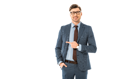 smiling businessman in glasses and suit pointing sideways isolated on white