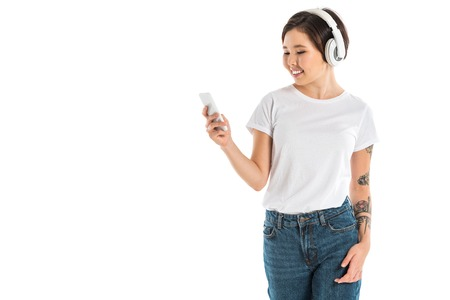 attractive young woman wearing headphones, listening music and using smartphone isolated on white Stok Fotoğraf