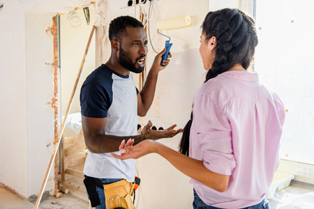young couple having quarrel while making renovation of home