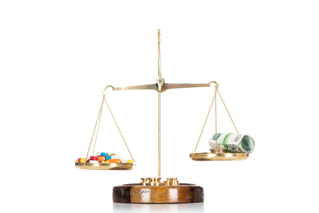 scales with various colorful pills and russian cash money isolated on white
