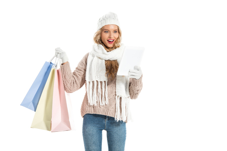excited woman with shopping bags using digital tablet isolated on white