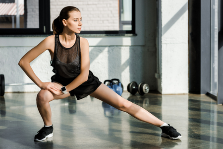 focused sportswoman doing lateral lunge exercise at fitness center