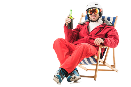 Happy man in red ski suit with beer bottle sitting in deck chair and smiling isolated on white 写真素材