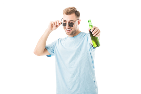 Cheerful man standing and holding bottle with beer isolated on white Stock Photo